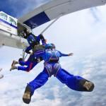 Een leerling vertrekt met twee instructeurs voor een parachutesprong